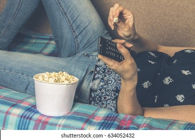 Women watching tv with popcorn at home in the living room. The concept of laziness.