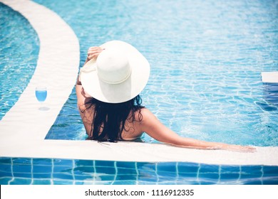 Women wear bikinis and drinking cocktails in the hot summer at the swimming pool.