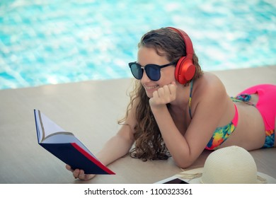 Women wear bikinis, read books and listen to music at the summer recreation pool.