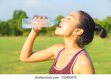 Women wear sports bra drink water after exercise.