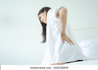 Women wear white shirts and pink pants on the bed in a room with hip pain in the morning.Asian women Have back pain In the morning.Back pain is caused by a mattress.Do not focus on objects.