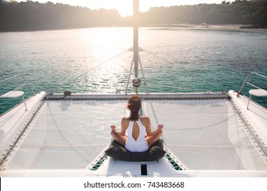 Women wear white swimsuits. Meditation on a catamaran sailboat. Private boat trips to the island and the beach on vacation, The women on the boat see the shore and the beach on the island.