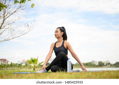 Women wearing black, practicing yoga for health at the park.