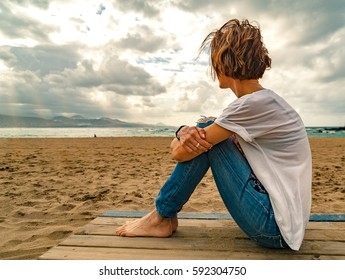 Women wearing denim jeans and white t-shirt sitting on a sandy beach overlooking scenic cloudy sky