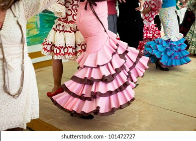 Women wearing flamenco dresses dancing sevillanas at Seville's Feria de Abril.