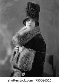 Women wearing fur lined velvet coat with opulent fur collar and cuffs. Her 1920s cloche hat is ornamented with ostrich feathers.