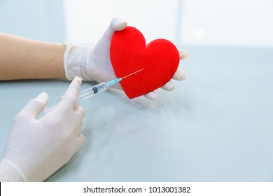 Women wearing gloves used syringes stabbed in the red heart.