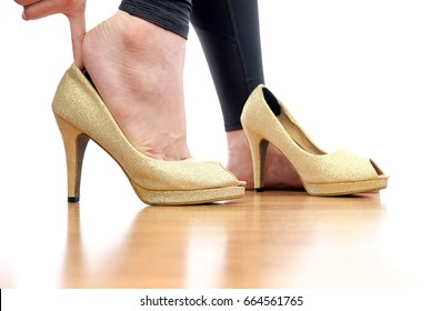 Women are wearing gold high heels. Her hand catches high heels.