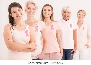 Women wearing pink shirts and breast cancer ribbons on white background