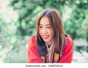 A women wearing a red robe on graduation day and she is very happy in university with bokeh background  at bangkok , Thailand
