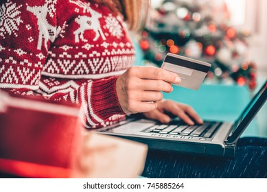 Women wearing red sweater sitting on the sofa and using laptop and credit card to shopping online at home