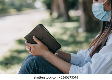 Women wearing surgical masks is praying with  Bible in park