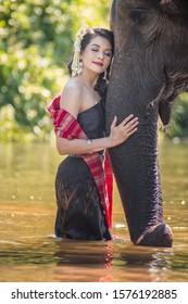 Women wearing thai dress hugging elephants
