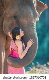 Women wearing Thai dress hugging elephants.
