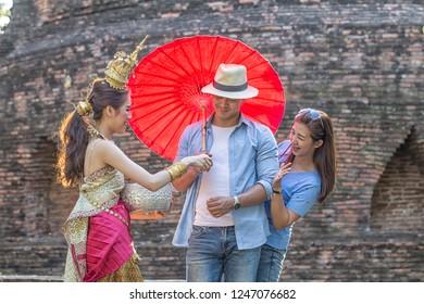 Women wearing Thai traditional dress splashing water with tourist during Songkran Festival at ayutthaya Thailand