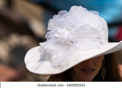 A women wearing a white lace decretive hat at a horse race.