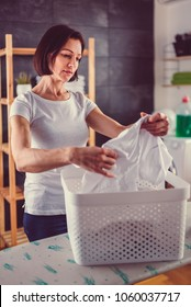 Women wearing white shirt checking wrinkles on clothes after washing and drying at laundry room