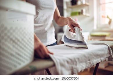 Women wearing white shirt ironing clothes on ironing board in laundry room at home