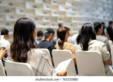 Women wearing white shirt with long hair sitting on the seat in seminar or meeting in conference room