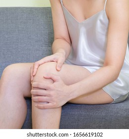 Women wearing white skirts pajamas  sitting on gray sofa.Female holding her hand to the waist and back, she felt pain,health care concept