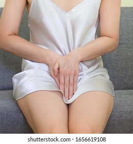 Women wearing white skirts pajamas  sitting on gray sofa.Female holding her hand to the Pussy, she felt pain,health care concept