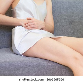 Women wearing white skirts pajamas sitting on gray sofa.Female holding her hand to the right belly, she felt pain,health care concept, Stomach ache