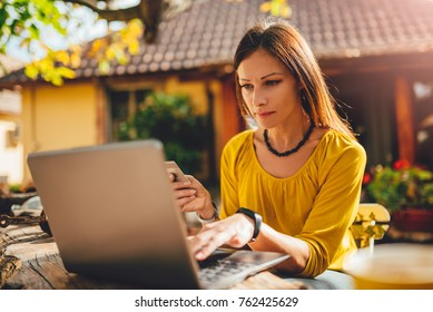 Women wearing yellow shirt sitting in the backyard patio, shopping online on laptop and using credit card