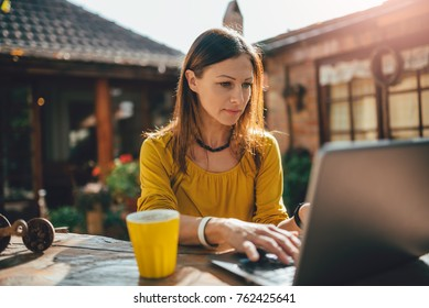 Women wearing yellow shirt using laptop at backyard patio