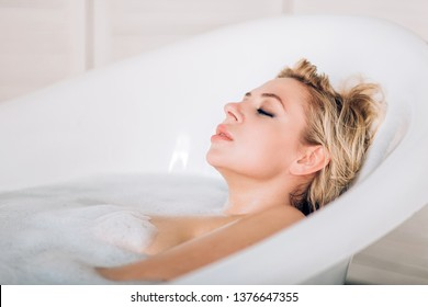 Women, wellness, relax concept. Closeup of pretty woman with healthy soft skin, blonde short hair closed eyes spending free time at bathroom, enjoying spa, resting in hot bath after work day at home