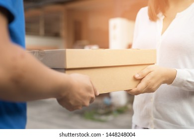 Women in white are receiving packages that are ordered online with officials in blue.