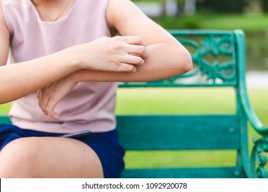 Women who are itching from insect bites in the grass. / Health care and medicine.