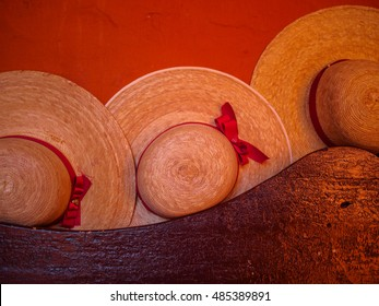 Women wicker hats with red lace on a bench