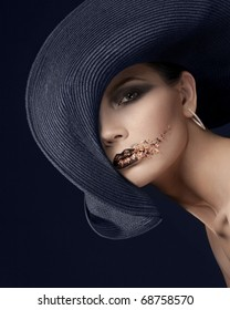 Women in wide hat with tinsel on her face