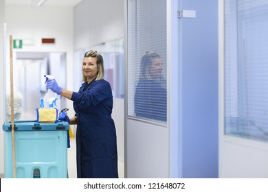 Women at work, portrait of happy professional female cleaner smiling and looking at camera in office. Three quarter length