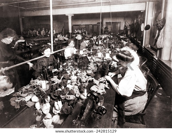 Women workers sewing teddy bears in an sweat shop assembly line. Women are engaged at the sewing machines, while men associated with the operation are in the background. New York City, 1915