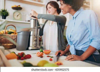 Women working at juice bar. Female putting fruits in juicer. Two young woman preparing juice .