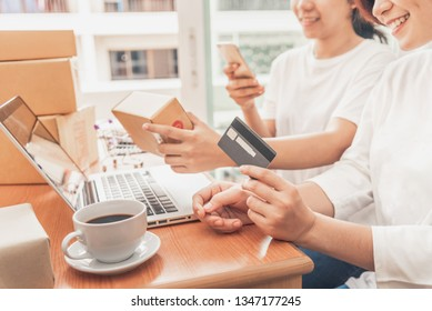 The women working laptop computer from home on wooden floor with postal parcel, Selling online ideas concept.