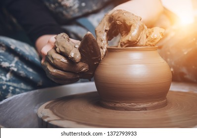 Women working on the potter's wheel. Hands sculpts a cup from clay pot. Workshop on modeling on the potter's wheel.