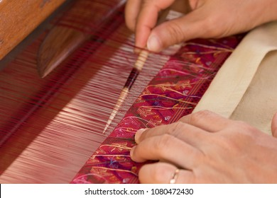 Women working on silk thread with traditional hand weaving loom