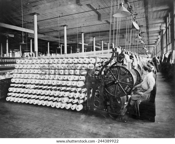 Mulheres trabalhando em máquinas têxteis, radiando e inspecionando fios, na American Woolen Company, Boston. O processo de transporte prepara a urdidura, as fibras longitudinais de um tecido tecido. Ca. 1910.