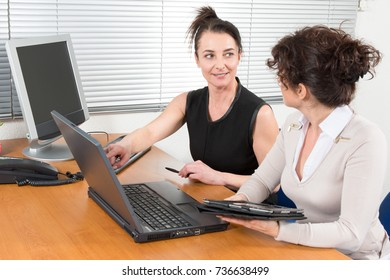 Women working together at desk in office interior