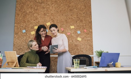 Women are working together in an office. One of the women is holding a digital tablet which they are all looking at.