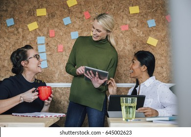 Women are working together in an office. They are talking and laughing as they use digital tablets.