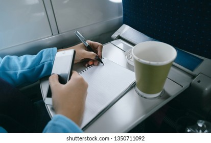 Women working while riding in a train. Women hands writing in a notebook