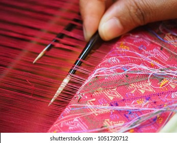 Women works on cotton or silk weaving with traditional hand weaving loom.