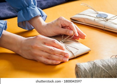women wrapping gift. A parcel wrapped in paper and tied with rough twine on yellow table