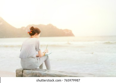 Women are writing on notebook at the beach