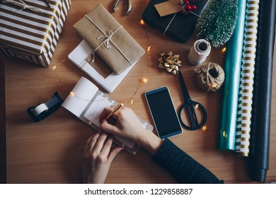 Women writing something down at gift wrapping table