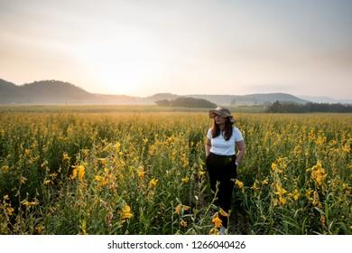 women in yellow flower field and sunrise landscape background