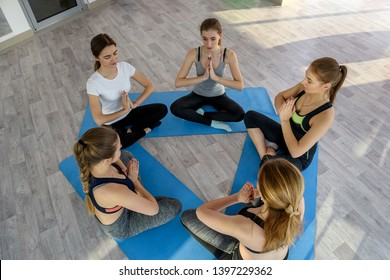Women in yoga class sitting in circle on the floor